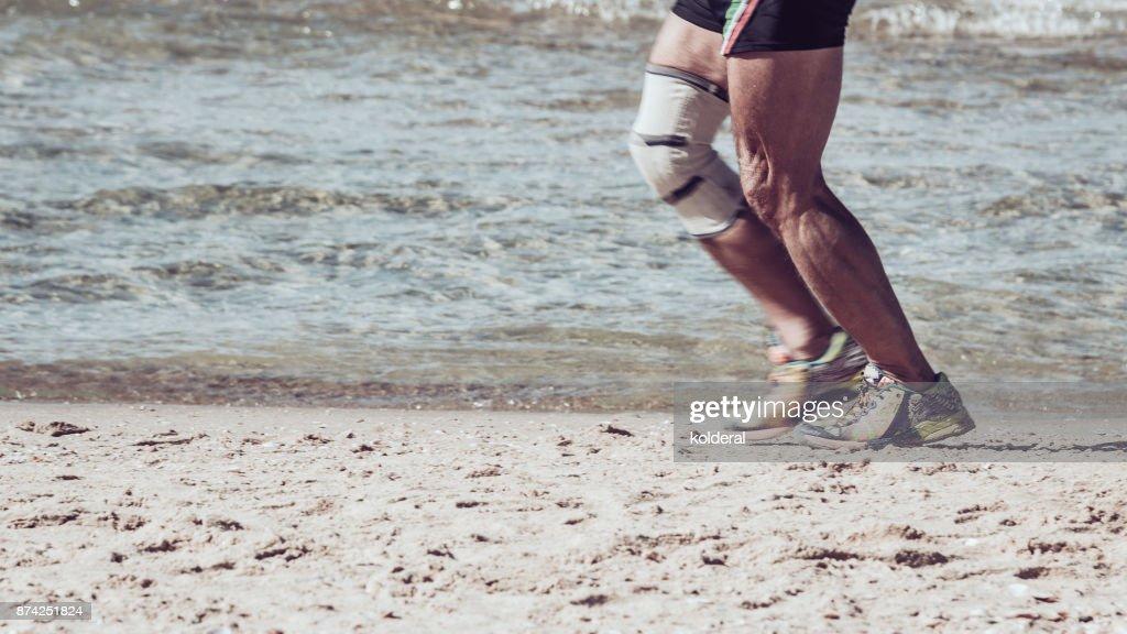 Senior with knee brace running on the beach : Stock Photo