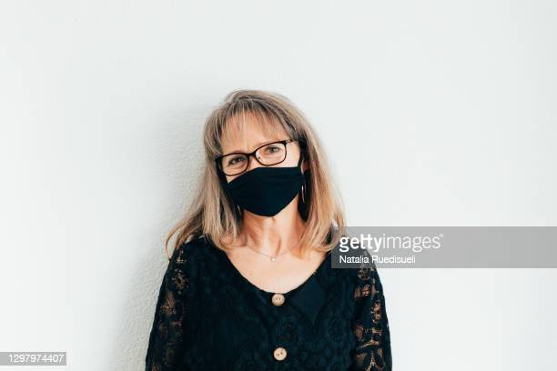 senior woman 50-55 years old wearing a black colored face protection and smiling. - 55 59 years stock pictures, royalty-free photos & images