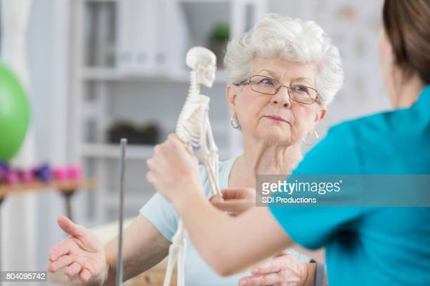 senior woman actively listens to therapist explain importance of posture - osteoporosis stock photos and pictures