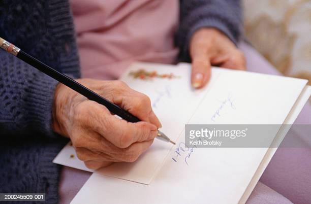 senior woman addressing letters, close-up of hand and pen - correspondentie stockfoto's en -beelden