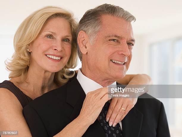 senior woman adjusting husband's necktie - ajustar imagens e fotografias de stock