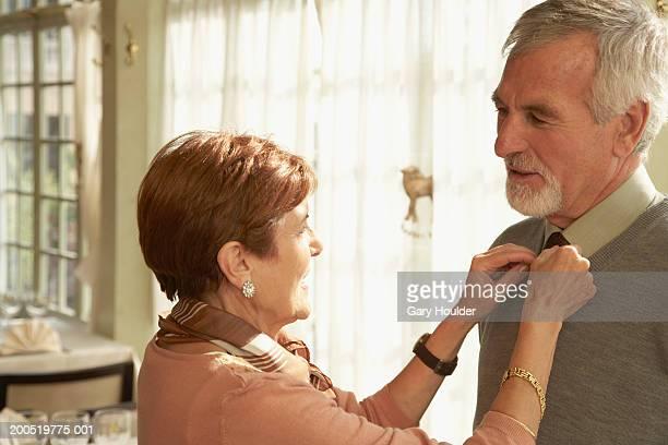 senior woman adjusting man's collar, smiling - ajustar imagens e fotografias de stock