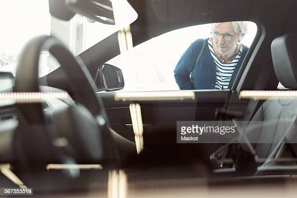 Senior woman admiring car displayed in store
