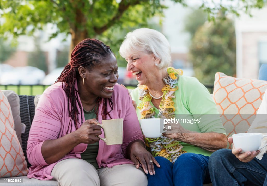 Senior woman, African-American friend laughing together : Stock Photo