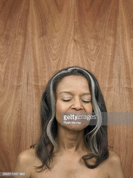 Senior woman against wood panelling, eyes closed, smiling