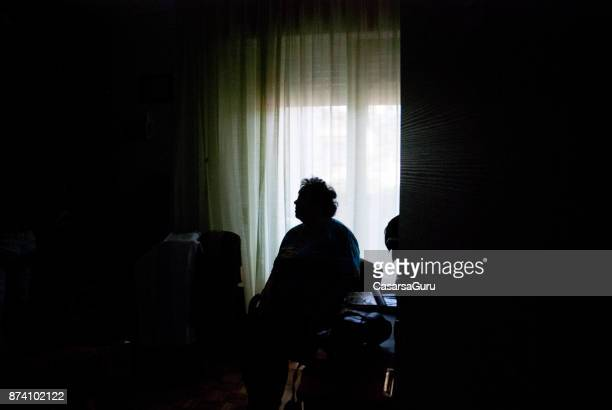 senior woman alone in dark room - loneliness stock pictures, royalty-free photos & images
