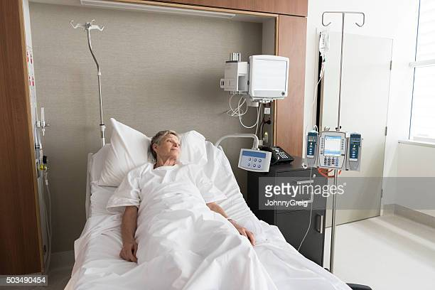 Senior woman alone in hospital bed looking out of window