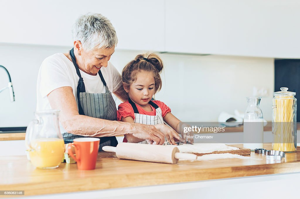 Senior woman and a small girl making cookies : Stock Photo