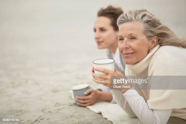 senior woman and adult daughter drinking coffee on the beach - pull à col montant photos et images de collection