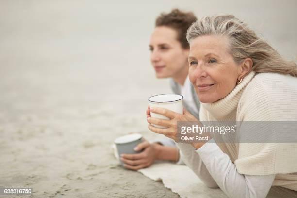 senior woman and adult daughter drinking coffee on the beach - blusa de gola rolê - fotografias e filmes do acervo