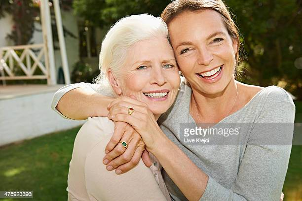 Senior woman and adult daughter embracing outdoors