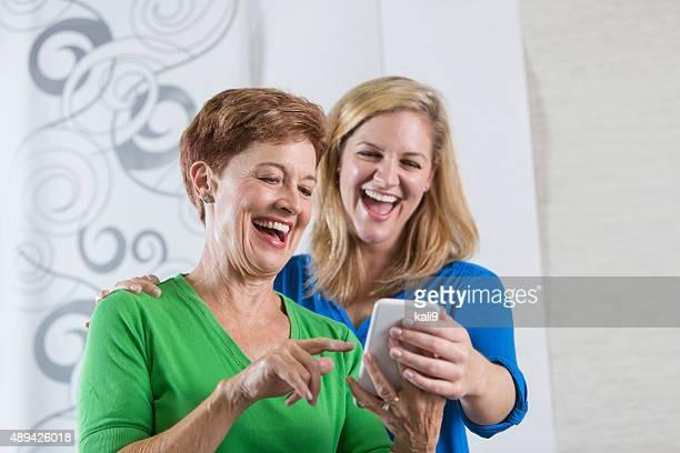 mulher sênior e filha adulta sorrindo no telefone - somente adultos - fotografias e filmes do acervo