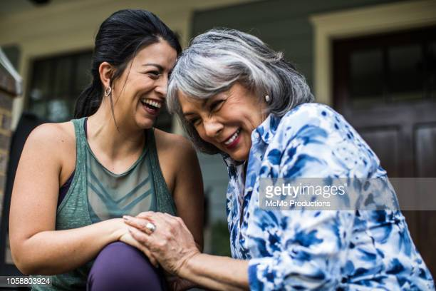 senior woman and adult daughter laughing on porch - daughter stock pictures, royalty-free photos & images