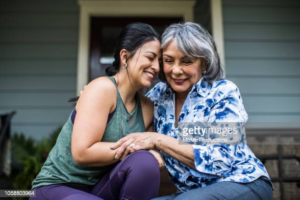 senior woman and adult daughter laughing on porch - sólo con adultos fotografías e imágenes de stock