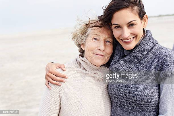 senior woman and adult daughter on the beach - two generation family stock pictures, royalty-free photos & images