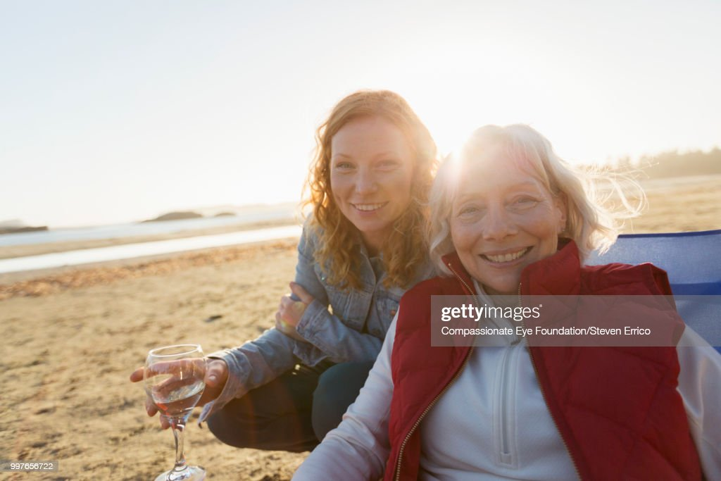Senior woman and adult daughter relaxing on beach at sunset : Stock Photo