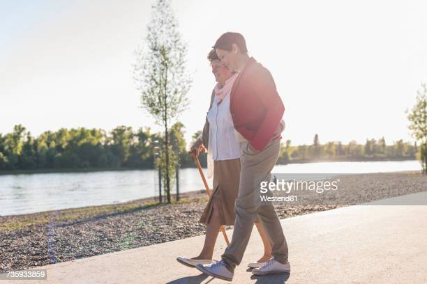 Senior woman and adult daughter strolling near river