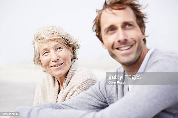 Senior woman and adult son on the beach