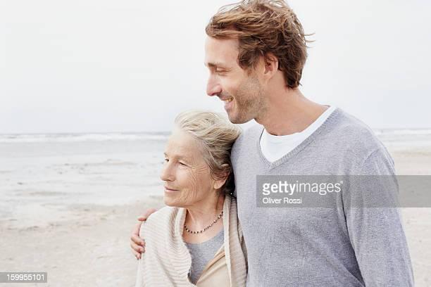 Senior woman and adult son on the beach