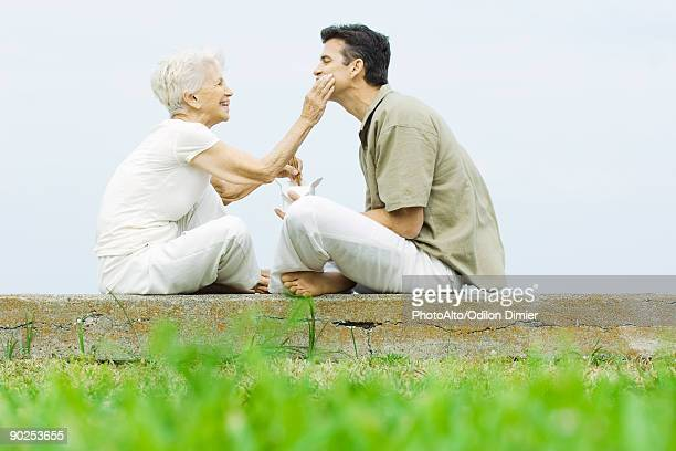 Senior woman and adult son sitting face to face outdoors, sharing take-out food