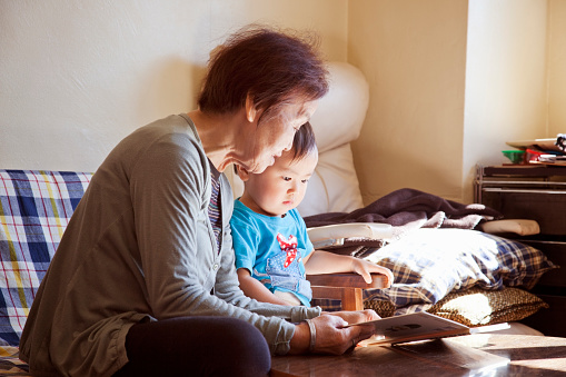 senior woman and baby boy reading a picture book - gettyimageskorea