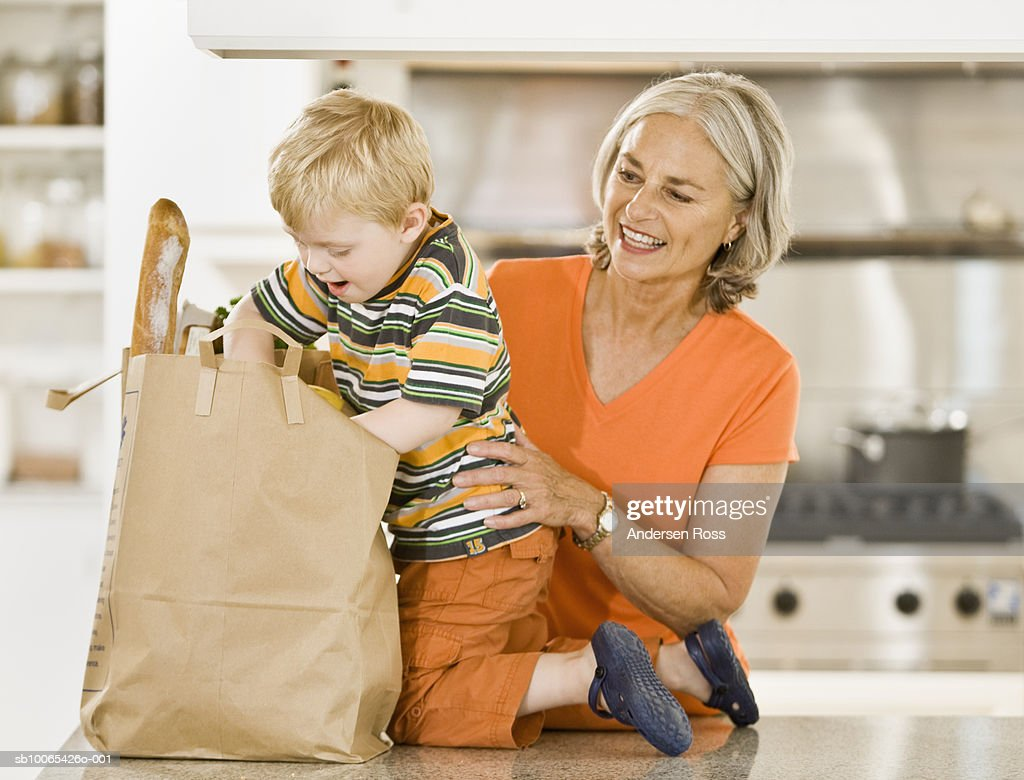 Senior woman and boy (2-3 years) unloading groceries : Foto stock