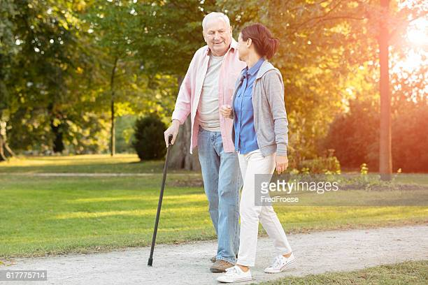 senior woman and caregiver go walking outdoors - walking cane stock photos and pictures