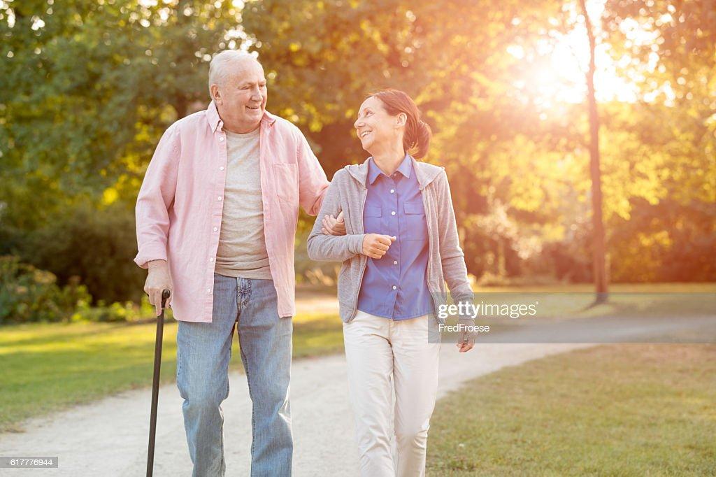 senior woman and caregiver go walking outdoors : Stock Photo
