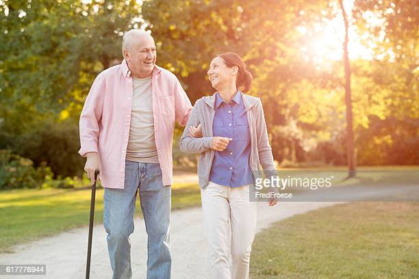 senior woman and caregiver go walking outdoors - 杖 ストックフォトと画像