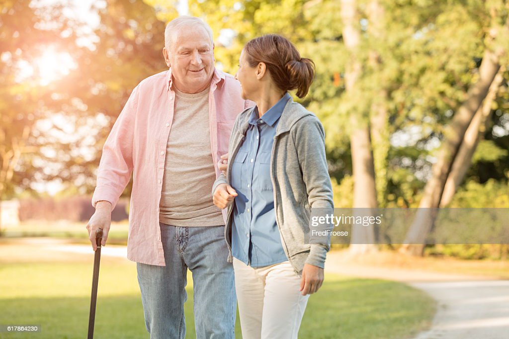 senior woman and caregiver go walking outdoors : Stock-Foto