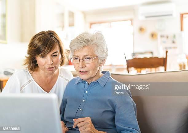 Senior woman and caretaker are using laptop