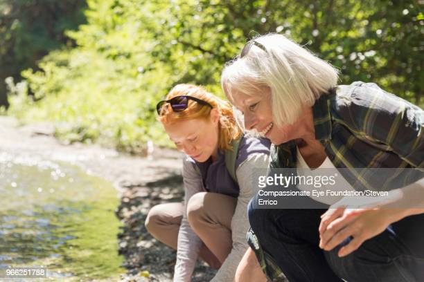 senior woman and daughter hiking crouching by river - hand on knee stock pictures, royalty-free photos & images