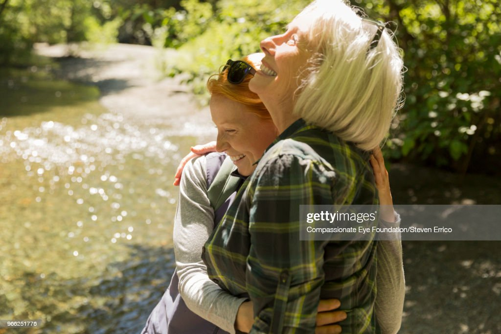 Senior woman and daughter hiking hugging by river : Stock Photo