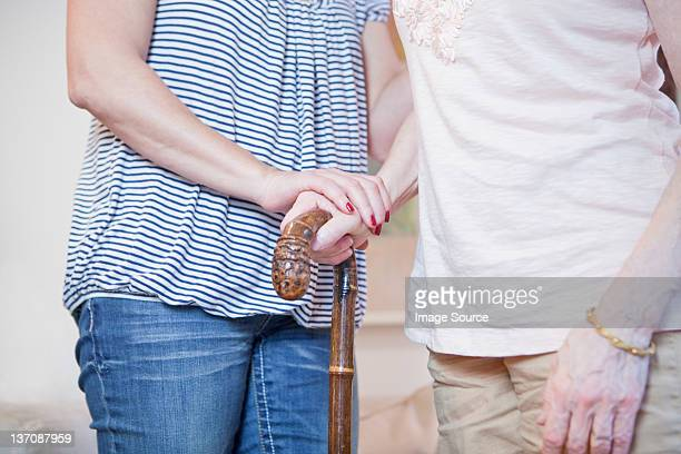 Senior woman and daughter holding walking stick