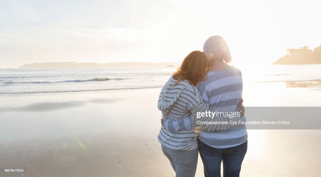 Senior woman and daughter hugging on beach looking at ocean view at sunset : Stock Photo