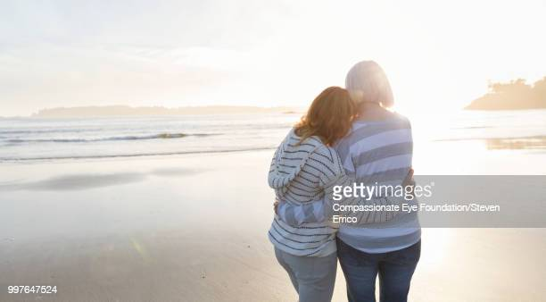 Senior woman and daughter hugging on beach looking at ocean view at sunset