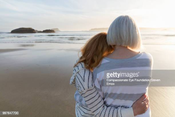 senior woman and daughter hugging on beach looking at ocean view at sunset - compassionate eye foundation stock pictures, royalty-free photos & images