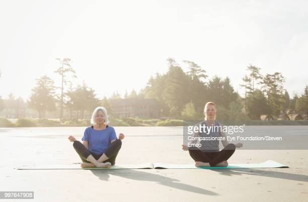 senior woman and daughter practicing yoga on beach - photography stock pictures, royalty-free photos & images