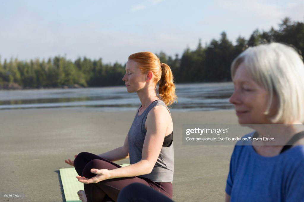 Senior woman and daughter practicing yoga on beach : Stock Photo