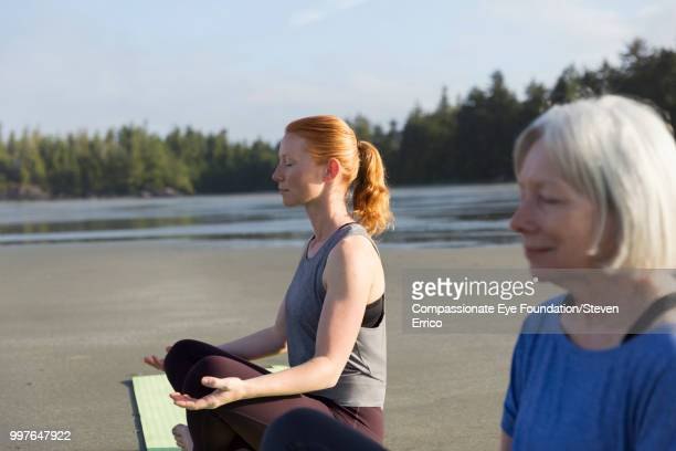 Senior woman and daughter practicing yoga on beach