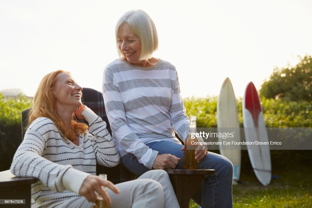 Senior woman and daughter relaxing in campsite garden : Stock Photo