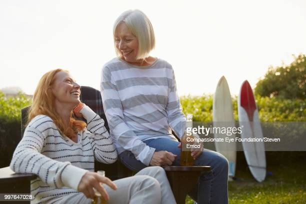 senior woman and daughter relaxing in campsite garden - older redhead stock pictures, royalty-free photos & images