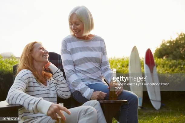 Senior woman and daughter relaxing in campsite garden