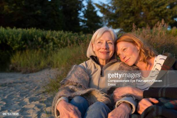 senior woman and daughter sitting on beach at sunset - cef do not delete stock pictures, royalty-free photos & images