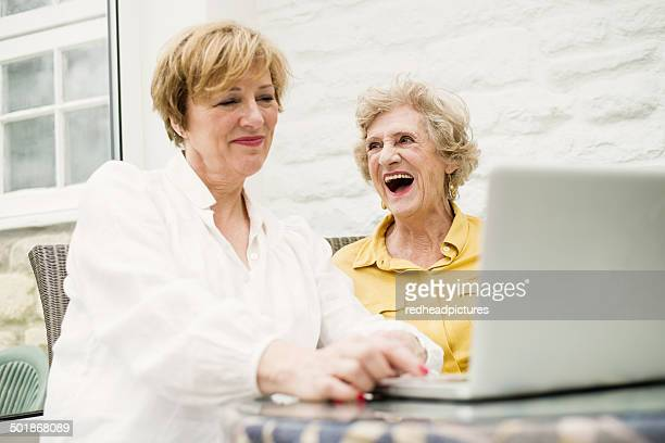 Senior woman and daughter, using laptop