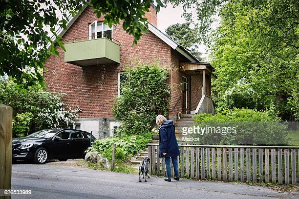 Senior woman and dog standing outside house
