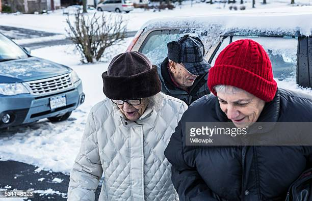 Senior Woman And Elderly Parents Walking From Car