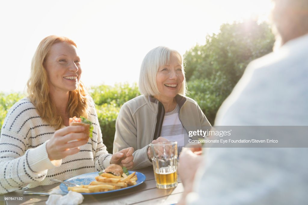 Senior woman and family enjoying lunch at campsite picnic table : Stock Photo