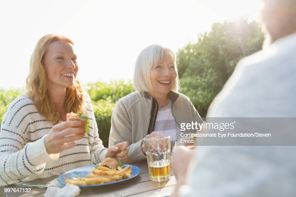 Senior woman and family enjoying lunch at campsite picnic table