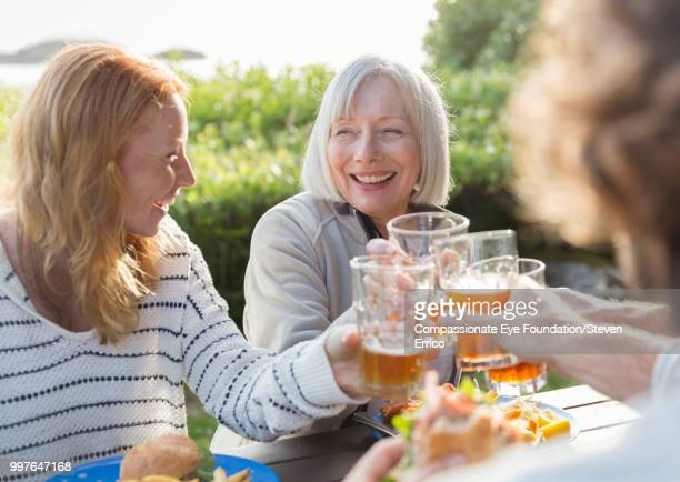 senior woman and family toasting with beer glasses at campsite picnic table - mother in law stock pictures, royalty-free photos & images
